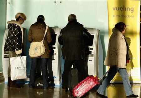 Passengers stand in front of a Vueling auto check-in at Barcelona's airport January 30, 2012. REUTERS/Gustau Nacarino
