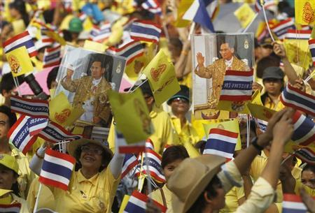 Well-wishers hold portraits of Thailand's King Bhumibol Adulyadej and wave the Thai national flag and the King's royal flag as they wait for the king to arrive for a ceremony outside the Anatasamakom Throne Hall in Bangkok December 5, 2012. REUTERS/Chaiwat Subprasom