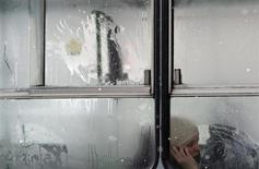 Женщина смотрит в окно автобуса в Будапеште 27 марта 2013 года. Российский монополист в экспорте газа - Газпром обещает поставить в четверг рекордные для конца марта 520 миллионов кубометров в сутки потребителям в Европе, сообщил Газпром в четверг. REUTERS/Laszlo Balogh