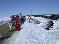 Crews work to recover an estimated 30,000 gallons of crude oil that leaked from three tanker cars involved in a derailment near Parkers Prairie in west central Minnesota March 27, 2013. REUTERS/Doug Bellfeuille/Minnesota Pollution Control Agency/Handout
