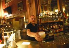 A waiter serves a drink at Cafe Savoy, which is a lesbian, a gay, bisexual and transgender (LGBT) cafe, in Vienna March 20, 2013. Vienna has joined a growing list of European cities seeking to attract lesbian and gay tourists who are expected to remain willing to spend on travel while other recession-hit travellers cut back. City authorities in Vienna this month released a review of the Austrian capital's gay and lesbian tourism strategy, deciding to focus on travellers interested in music, culture and history -- and with money to spend. Picture taken March 20, 2013. REUTERS/Leonhard Foeger
