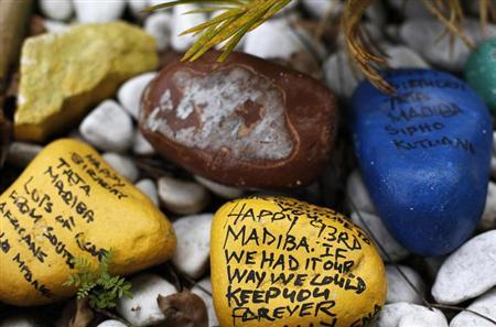 Painted stones with messages wishing former South African President Nelson Mandela a happy birthday are seen in the garden outside his house in Houghton, Johannesburg March 28, 2013. REUTERS/Siphiwe Sibeko
