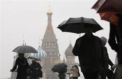 Люди с зонтами на Красной площади в Москве 27 октября 2009 года. Рабочая неделя в Москве будет теплее предыдущих, но обещает столичным жителям облачную погоду и дожди, прогнозируют синоптики. REUTERS/Denis Sinyakov