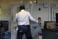 Сотрудник отделения Bank of Cyprus в Никосии открывает сейф, 28 марта 2013 года. Крупные вкладчики самых больших банков Кипра потеряют около 60 процентов сбережений, превышающих 100.000 евро, подтвердил центробанк страны. REUTERS/Yannis Behrakis