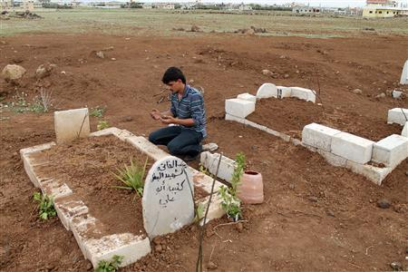 A man prays at the grave of a Free Syrian Army fighter at a cemetery at al-Karak al-Sharqi in Deraa March 30, 2013. Picture taken March 30, 2013. REUTERS/Thaer Abdallah