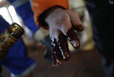 Рабочий Намик Алиев проверяет качество нефти на платформе в Каспийском море 22 января 2013 года. Нефть дешевеет из-за новых опасений по поводу темпа экономического роста США - крупнейшего в мире потребителя топлива. REUTERS/David Mdzinarishvili