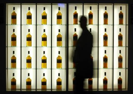 A visitor walks past an alcohol stand during the TFWA (Tax Free World Association) exhibition in Cannes, southeastern France, October 19, 2009. REUTERS/Eric Gaillard/Files