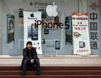 Мужчина сидит перед магазином Apple в Пекине, 2 апреля 2013 года. Исполнительный директор Apple Inc Тим Кук принес в понедельник извинения китайским потребителям в ответ на критику со стороны государственных средств массовой информации в адрес американской компании из-за условий гарантийного обслуживания смартфонов iPhone. REUTERS/Kim Kyung-Hoon