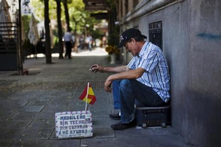 Manuel Sastre, 59, smokes a cigarette as he asks for money in central Madrid July 31, 2012. REUTERS/Susana Vera