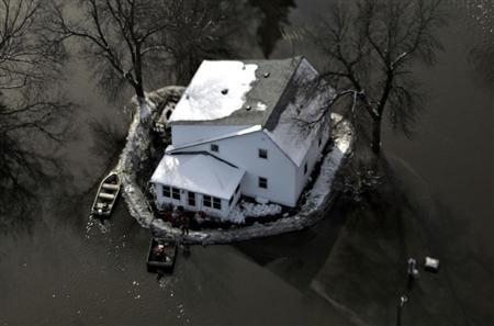 An aerial view shows a house with a sandbag levee is surrounded by floodwaters south of Fargo, North Dakota in this file photo taken March 29, 2009. REUTERS/Allen Fredrickson