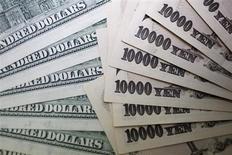 Купюры по 10.000 иен и $100, сфотографированные в Токио, 9 сентября 2010 года. Курс иены резко снизился после объявления Банком Японии решительных мер стимулирования экономического роста. REUTERS/Yuriko Nakao