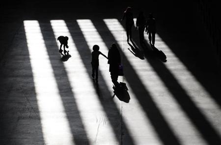 Visitors to Tate Modern walk through sunlight shining through the windows in London July 30, 2009. REUTERS/Andrew Winning
