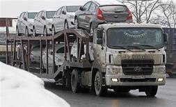 Грузовик везет новые автомобили Hyundai около Санкт-Петербурга 6 февраля 2013 года. Российский производитель иномарок группа компаний Автотор ведет переговоры с банками, чтобы занять 50-60 миллиардов рублей на масштабный проект строительства 22 автозаводов в Калининградской области. REUTERS/Alexander Demianchuk