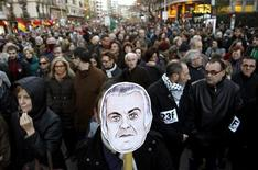 A man holds a picture of former People's Party (PP) treasurer Luis Barcenas investigated for bribery during a demonstration against austerity measures and political corruption in Valencia, February 23, 2013. REUTERS/Heino Kalis