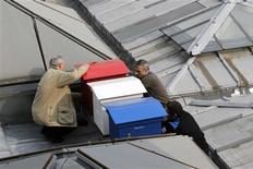 Beekeepers and employees install three beehives in the blue, white, red colours of the French national flag on the roof of the National Assembly in Paris April 3, 2013. REUTERS/Jacky Naegelen