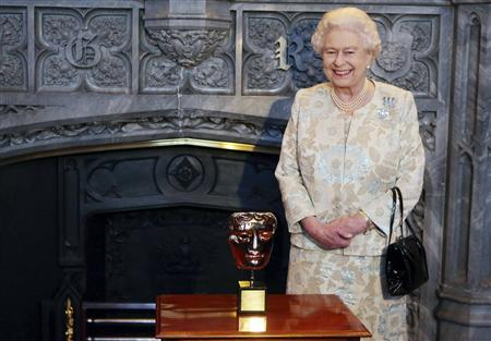 Britain's Queen Elizabeth poses with her honorary British Academy of Film and Arts (BAFTA) award, after receiving it from actor Kenneth Branagh in recognition of a lifetime's support of British film and television, during a reception for the British Film Industry at Windsor Castle in southern England April 4, 2013. REUTERS/Steve Parsons/pool