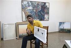 Imran Mudassar, 31, a fine art teacher, shows his latest piece during an interview with Reuters at Government College University in Lahore March 22, 2013. REUTERS/Mohsin Raza