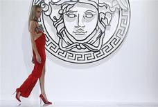 """Топ-модель дома Versace показывает наряд из коллекции осень-зима 2013 на Неделе выскокой моды в Милане, 22 февраля 2013 года. Итальянский модный дом Versace, один из последних крупных производителей товаров класса """"люкс"""", оставшихся во владении семьи основателя, может склониться к продаже части акций инвесторам с целью финансирования расширения бизнеса в Азии. REUTERS/Tony Gentile"""