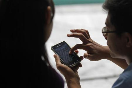 A couple uses a mobile phone on the side of a street in Yangon, March 7, 2013. REUTERS/Soe Zeya Tun /Files