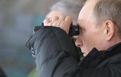 Президент России Владимир Путин наблюдает за военными учениями под Краснодаром 29 марта 2013 года. Путин отругал ЕС за кипрский кризис в преддверии визита в Германию и Нидерланды, где политики ждут его объяснений по поводу рейдов силовиков в правозащитные организации и процесса над мёртвым Магнитским. REUTERS/Mikhail Klimentyev/RIA Novosti/Pool