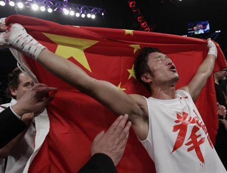 China's Zou Shiming, two-time Olympic gold medal winner and three-time World Amateur Champion, celebrates his win with a Chinese national flag after beating Mexico's Eleazar Valenzuela during his professional debut at Cotai Arena inside Venetian Macao in Macau early April 7, 2013. REUTERS/Bobby Yip
