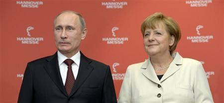 German Chancellor Angela Merkel and Russian President Vladimir Putin pose for photographers before they officially open the Hanover Messe, industrial trade fair, in Hanover April 7, 2013. REUTERS/Fabian Bimmer