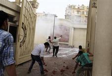 Египетские копты-христиане кидают камни с территории главного собора в Каире в находящихся за его пределами мусульман 7 апреля 2013 года. Как минимум один человек погиб, более 80 получили ранения в результате массовых столкновений между египетскими христианами и мусульманами в центре Каира в воскресенье. REUTERS/Asmaa Waguih
