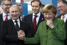 Президент России Владимир Путин и канцлер Германии Ангела Меркель на ярмарке в Ганновере 8 апреля 2013 года. Путин высмеял протест, с которым выступили полуобнажённые феминистки в Германии, пошутив, что ему понравилось увиденное, и резко отверг критику по поводу своего отношения к правам человека. REUTERS/Fabrizio Bensch