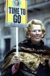 Лондонский демонстрант в маске Маргарет Тэтчер держит плакат, празднуя её уход в отставку 22 ноября 1990 года. Фото иллюстрирует воспоминания Дэвида Стори - который был политическим корреспондентом Рейтер в Лондоне в последние месяцы премьерства Тэтчер, умершей сегодня - о её драматическом уходе из активной политики в ноябре 1990-го. REUTERS/Kevin Lamarque