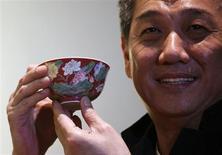 """Negociante de Hong Kong William Chak posa com a tijela de porcelana após arrematá-la em leilão da Sotheby's em Hong Kong. A tigela """"falangcai"""" rubi-terra com duplo-lotus do período Kangxi, entre 1662 e 1722, foi arrematada nesta segunda-feira por 74 milhões de dólares, quebrando um recorde para porcelana chinesa do período Kangxi. REUTERS/Bobby Yip"""