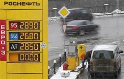 Автомобили проезжают мимо АЗС Роснефти в Москве 21 марта 2012 года. Минфин РФ, озабоченный сокращением поступлений в бюджет из-за перехода нефтекомпаний на более экологичное топливо с пониженной ставкой акцизов, планирует перекроить налогообложение отрасли, сказал министр финансов РФ Антон Силуанов. REUTERS/Denis Sinyakov
