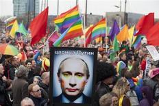 Участник акции протеста гей-сообщества Амстердама держит портрет Владимира Путина с подрисованным лицом 8 апреля 2013 года. Гражданские активисты продолжили привлекать внимание к проблеме прав человека в России в ходе европейского турне Владимира Путина, которого в Амстердаме встретило не менее тысячи борцов за права сексуальных меньшинств. REUTERS/Cris Toala Olivares