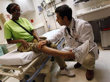 Patient Sharon Dawson Coates has her knee examined by Dr. Narang at University of Chicago Medicine Urgent Care Clinic in Chicago, June 28, 2012. REUTERS/Jim Young