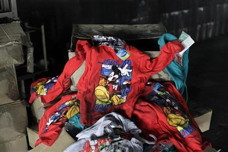 Clothes printed with Disney characters are seen among debris in the Tazreen Fashions garment factory, where 112 workers died in a devastating fire last month, in Savar November 30, 2012. REUTERS/Andrew Biraj