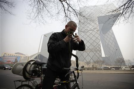 Artist Matt Hope adjusts the helmet linked to his air filtration bike in front of the China Central Television (CCTV) building on a hazy day in Beijing, March 26, 2013. REUTERS/Petar Kujundzic