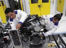 Technicians work on an engine during a media tour at the inauguration of Volkswagen's 100th plant worldwide in Silao in this January 15, 2013 file photo. Made in Mexico is increasingly more likely to mean cars than clothes as the country's manufacturing sector moves away from the low-skill, high-volume production lines of the past toward more sophisticated products. Picture taken January 15, 2013. To match Feature MEXICO-ECONOMY/MANUFACTURING REUTERS/Mario Armas/Files