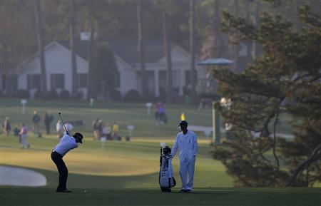 Defending champion Bubba Watson of the U.S. (L) hits his approach shot to the first green during a practice round in preparation for the 2013 Masters golf tournament at the Augusta National Golf Club in Augusta, Georgia, April 9, 2013. REUTERS/Brian Snyder