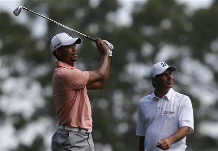 Tiger Woods of the U.S. (L) watches his tee shot on the third hole next to compatriot Fred Couples during a practice round in preparation for the 2013 Masters golf tournament at the Augusta National Golf Club in Augusta, Georgia, April 9, 2013. REUTERS/Phil Noble