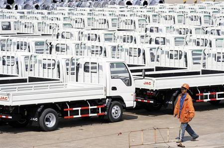 A worker walks past Chinese trucks for exporting at a port of Liangyungang, Jiangsu province, March 31, 2013. REUTERS/China Daily