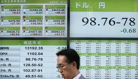 Мужчина проходит мимо информационного табло с курсами валют в Токио, 9 апреля 2013 года. Иена держится вблизи четырехлетнего минимума к доллару, которому, однако, пока не удается преодолеть рубеж 100 иен. REUTERS/Toru Hanai