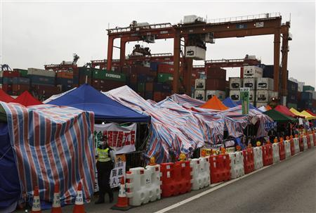 A policeman walks past tents set up by protesting dock workers during a strike outside Kwai Chung container terminal, which is operated by Hong Kong International Terminals Ltd., in Hong Kong April 10, 2013. REUTERS/Bobby Yip