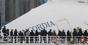 Relatives of victims stand on a ferry in front of the capsized cruise liner Costa Concordia outside Giglio harbour January 13, 2013. REUTERS/Tony Gentile