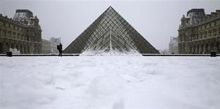 People enjoy the snow in front of Paris landmark, the Pyramid of the Louvre Museum, January 20, 2013, after several inches of snow fell on the French capital halting bus transportation and closing public parks. REUTERS/Christian Hartmann