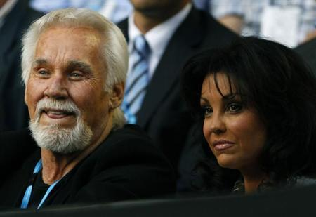Singer Kenny Rogers and his wife Wanda Miller watch the match between Rafael Nadal of Spain and Marin Cilic of Croatia at the Australian Open tennis tournament in Melbourne January 24, 2011. REUTERS/Tim Wimborne