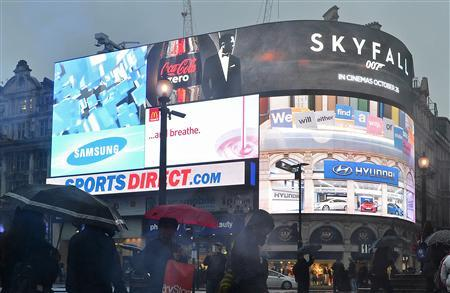 Shoppers pass an advertisement for the forthcoming James Bond film, Skyfall, on the electronic screens at Piccadilly Circus in central London October 21, 2012. REUTERS/Toby Melville