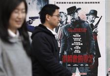 "People walk past a poster of the film ""Django Unchained"" outside a cinema in Beijing, April 11, 2013. REUTERS/Jason Lee"