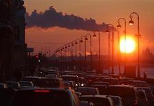 Дым над трубами ТЭС на фоне закатного солнца в стоящем в пробках Санкт-Петербурге 15 февраля 2011 года. Министерство экономики понизило прогноз роста ВВП России в текущем году до 2,4 процента с 3,6 процента, сказал замминистра Андрей Клепач. REUTERS/Alexander Demianchuk