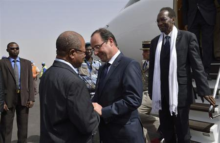 French President Francois Hollande (C) shakes hands with Malian Prime minister Django Sissoko (L) as Mali's interim president Dioncounda Traore (R) stands near at the Bamako airport February 2, 2013. REUTERS/Eric Feferberg/Pool