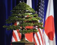 Дерево бонсай стоит на фоне флагов США и Японии в Вашингтоне, 30 апреля 2012 года. Япония и США приняли соглашение, позволяющее Токио присоединиться к Транстихоокеанскому партнерству(TPP) и переговорам о свободной торговле, чему премьер-министр Синдзо Абэ придает огромное значение в рамках стратегии по стимулированию роста экономики. REUTERS/Jonathan Ernst