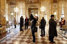 Visitors take pictures of furniture displayed for auction at the Hotel de Crillon in Paris April 12, 2013. REUTERS/Charles Platiau